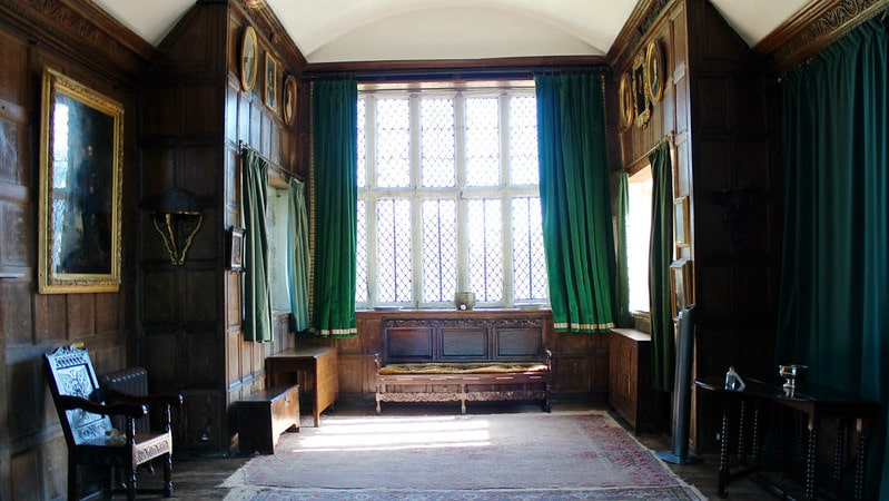 A hallway in a manor house furnished with long green curtains and antique wooden furniture.