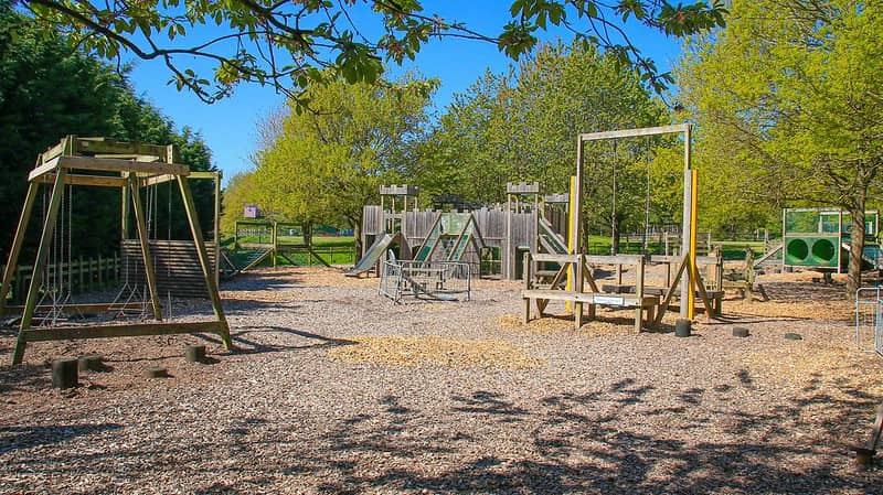 A wooden play area at Robin Hoods Wheelgate Park with swings, slides and tunnels.