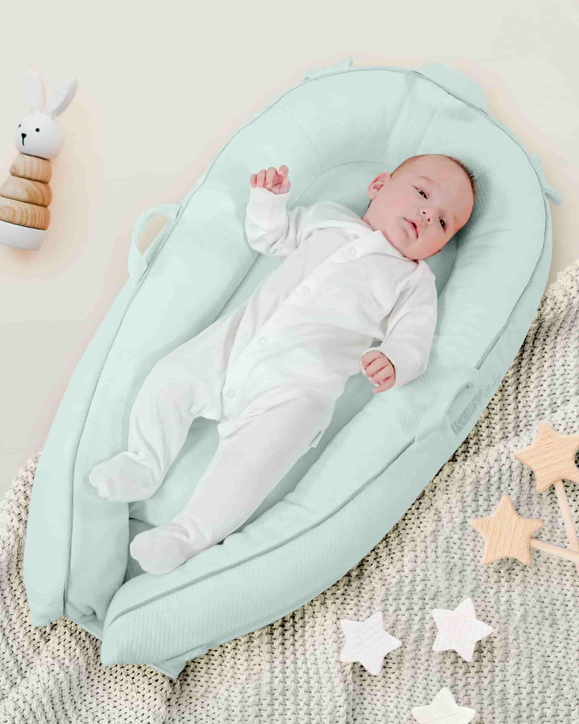 Adorable baby lying down in the smooth blue pod.