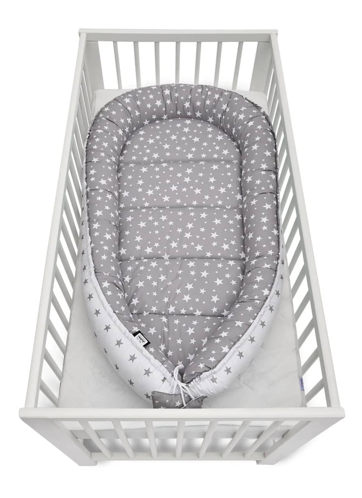 Elegant grey stars baby nest cocoon inside the crib.