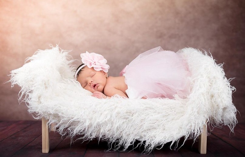 Baby in pink dress sleeping in the fur pod.