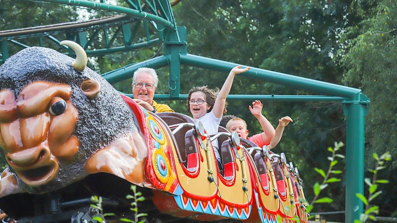A family enjoying a buffalo ride, smiling and holding their arms up, at the Twinlakes Theme Park.