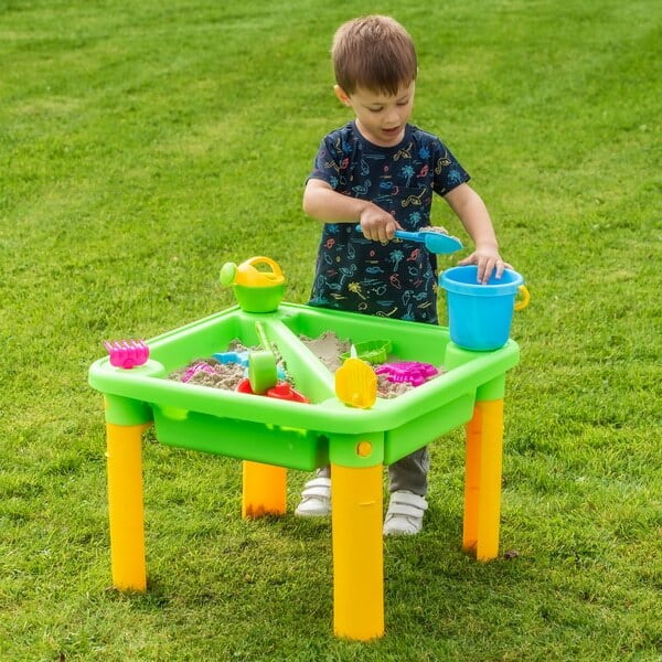 Little boy playing sand in the green splash and sand table.