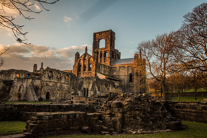 Kirkstall Abbey Monastery ruins during afternoon sunset.