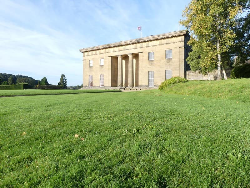 The exterior of Belsay Hall surrounded by green grass and trees.