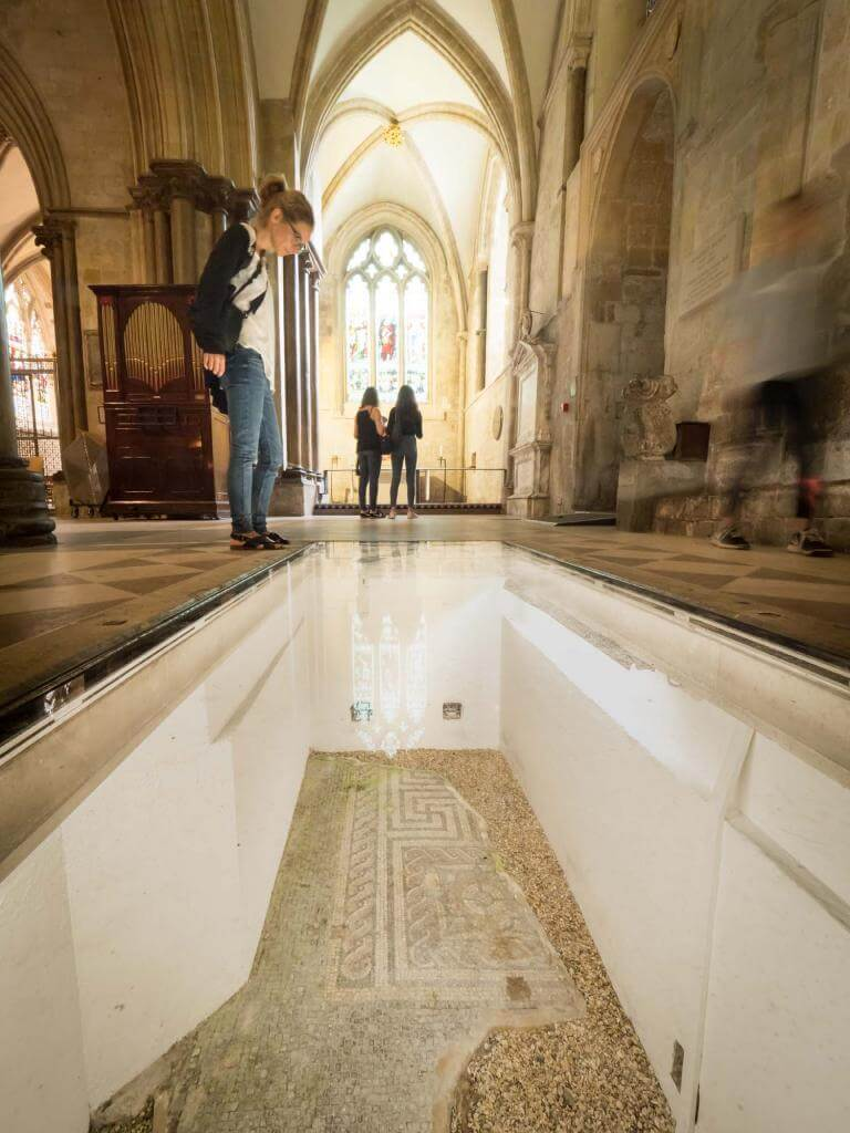 A visitor looking at some of the ancient remains on the floor of Chichester Cathedral.