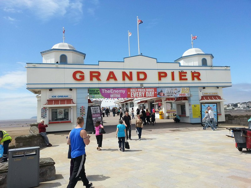 The entrance to the Grand Pier on Weston-super-Mare beach with people walking in and out.