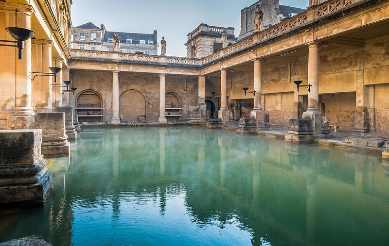 A view of the blue-green water and the surrounding columns of the Great Bath at the Roman Baths.