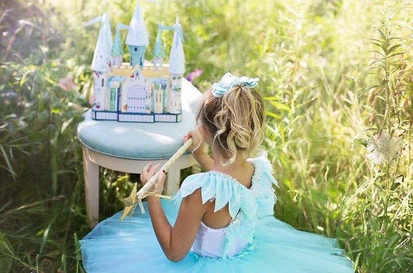 Little girl in blue fairy gown sitting in the grass with her mini blue castle.