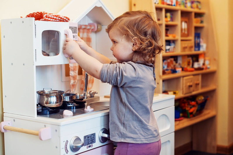 Little girl playing cooking in her mini kitchen.