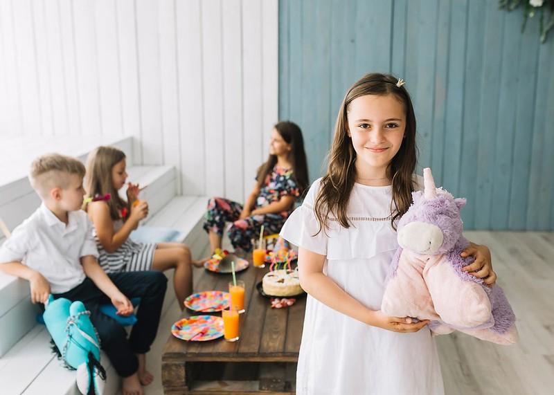 Girl in white dress carrying unicorn stuff toy.