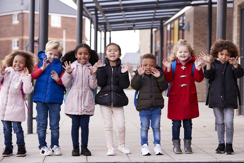 Group of toddlers standing and smiling in a row wearing coat and schoolbag.
