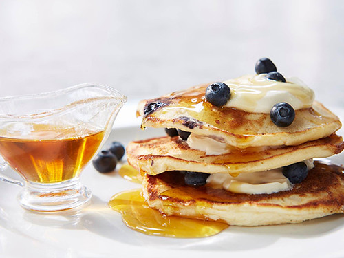 A stack of blueberry pancakes with frosting and syrup.
