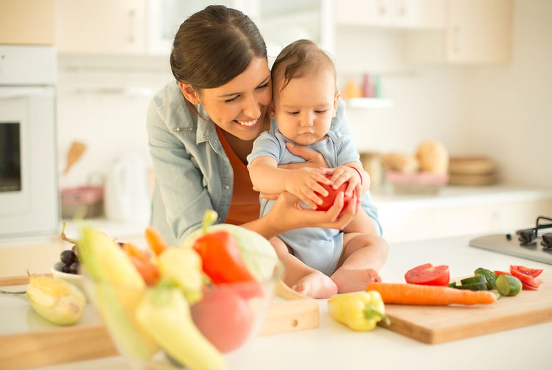 Mother introducing her baby to fruit and vegetables.