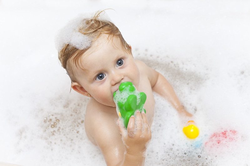 Baby bathing while playing his toy.