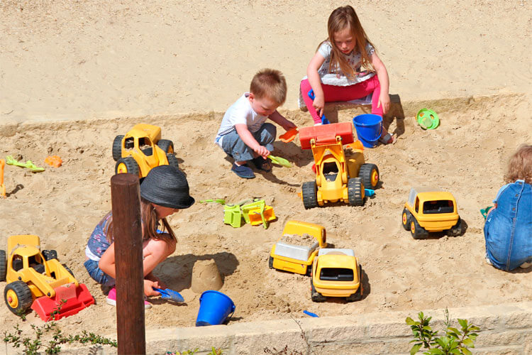 Kids playing with digger toys in the sandpit at Fairytale Farm.