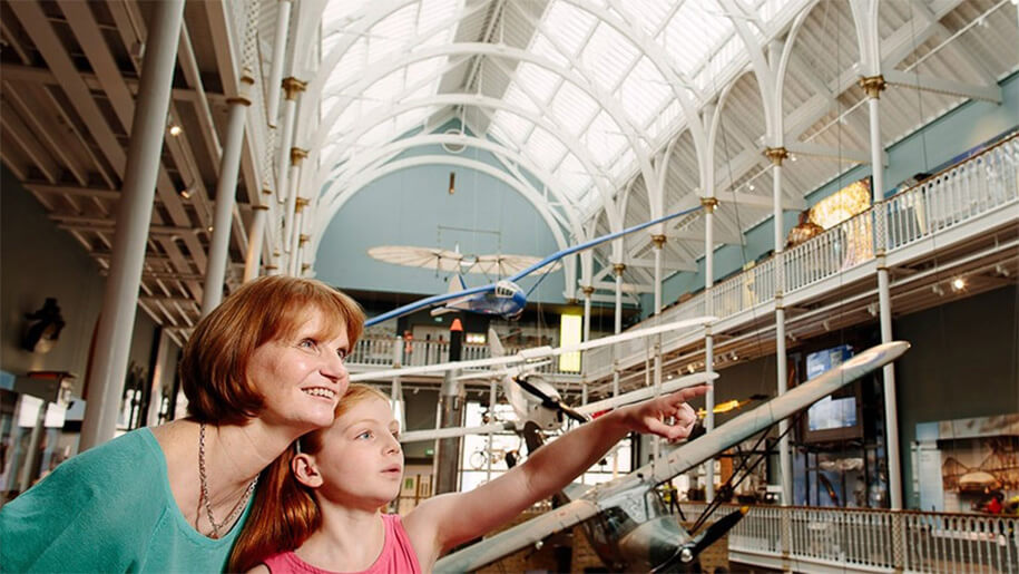 Mum and daughter pointing in the Grand Gallery at the National Museum of Scotland.