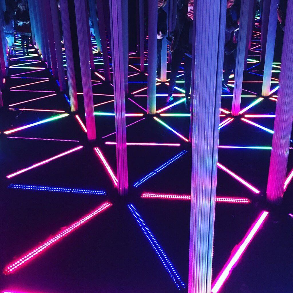 The Mirror Maze at Camera Obscura and World of Illusions, lit darkly with pink and purple neon lights.