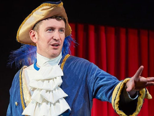 The main character on stage in the show Potted Panto dressed up as a prince.