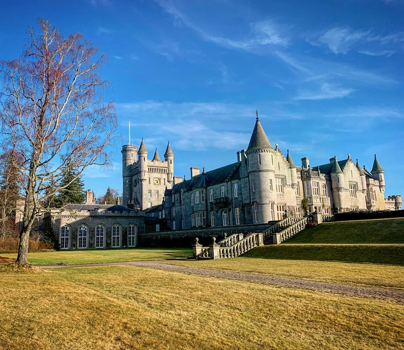 Balmoral Castle exterior with lawn in front of castle and blue skies.