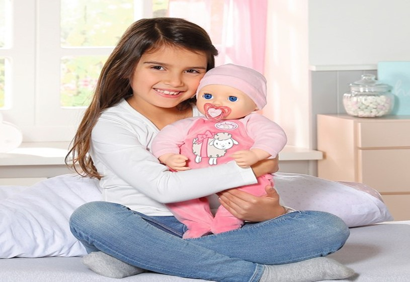 Girl holding doll while sitting in the bed.
