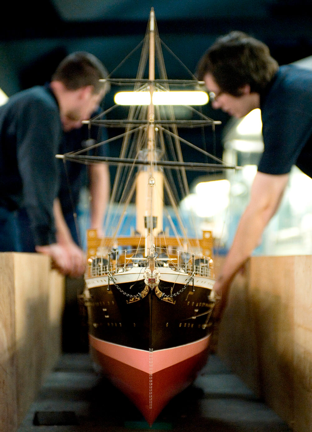 Two staff members at Riverside Museum holding a large model of a ship.