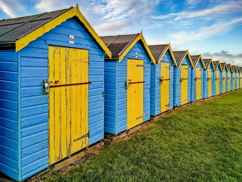 Colourful blue and yellow beach huts lined up on the grass at Bognor Regis Beach.