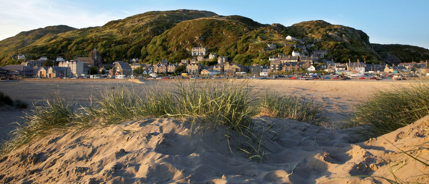 A view of the sand dunes at Traeth Abermaw Beach (Barmouth Beach), with the town and hills in the background.