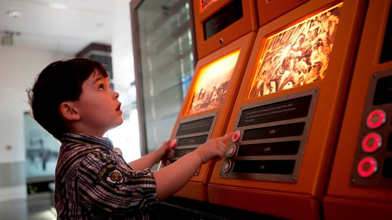 A small boy playing on one of the interactive learning machines at the National Waterfront Museum.