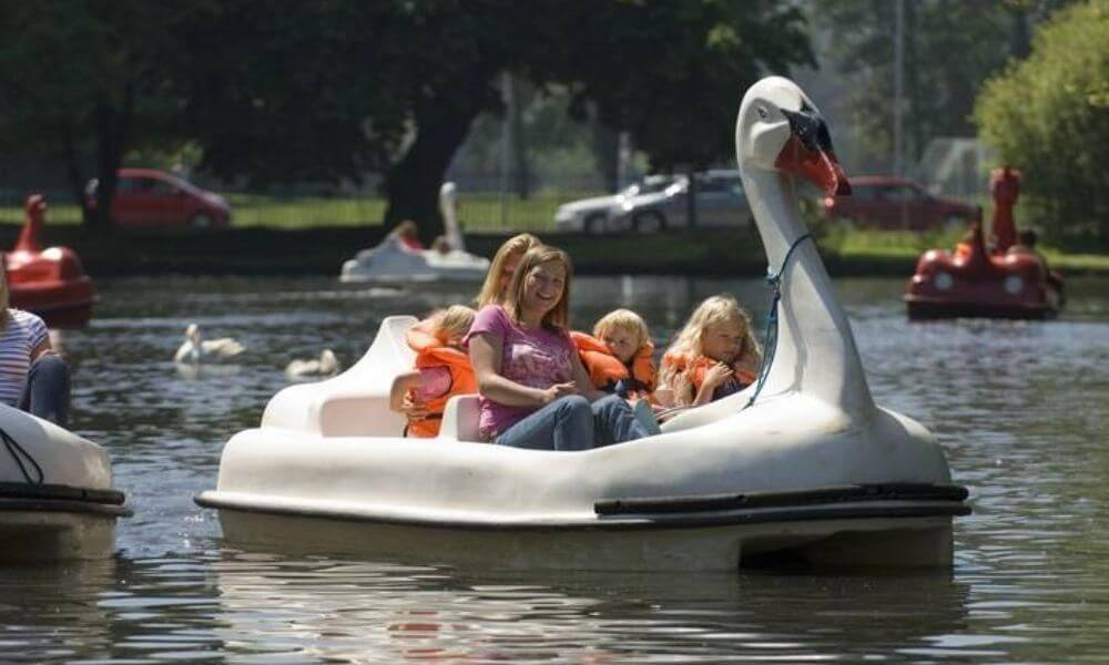 A family on a swan-shaped pedalo at Singleton Park boating lake.