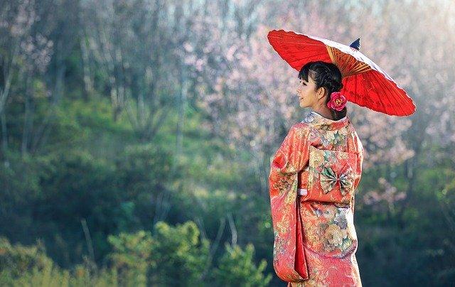 Beautiful Japanese maiden wearing a red kimono.