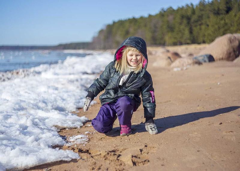 Finnish girl happily playing at the sea shore.