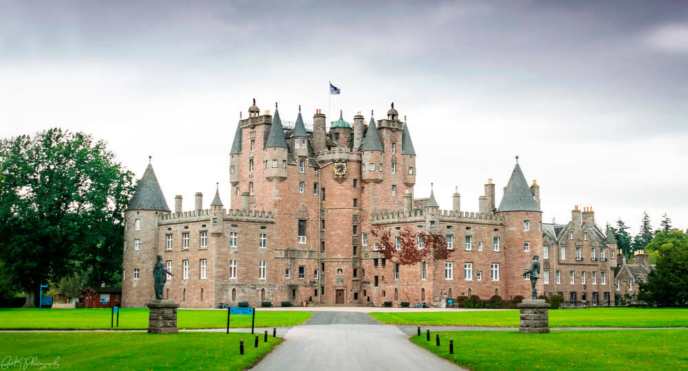 An outside view of Glamis Castle and the green grass of the grounds surrounding it.
