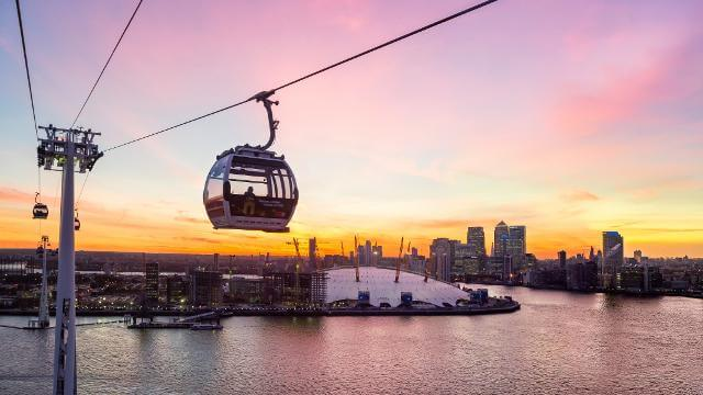 A cable car at Emirates Air Line against the London skyline, with a pink sunset.