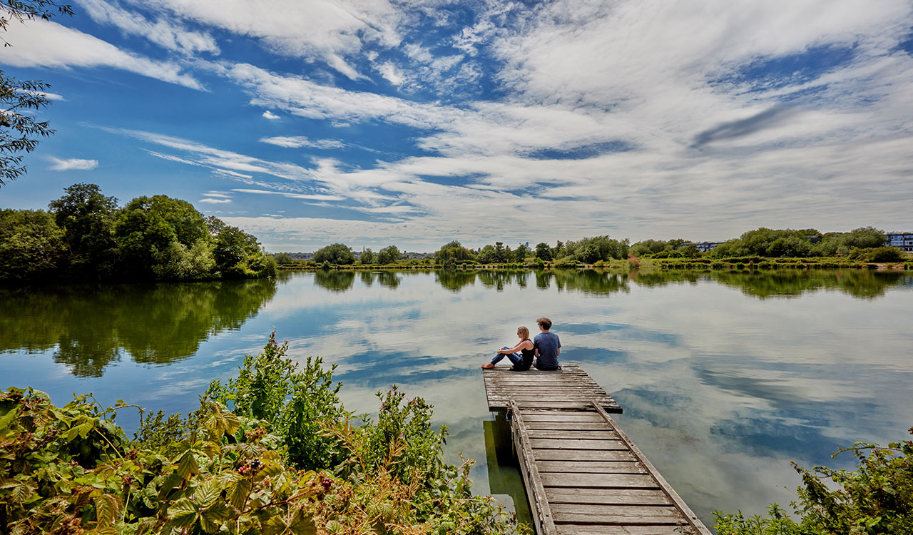 A couple sitting next to Walthamstow Wetlands, with the blue sky reflecting on the water.