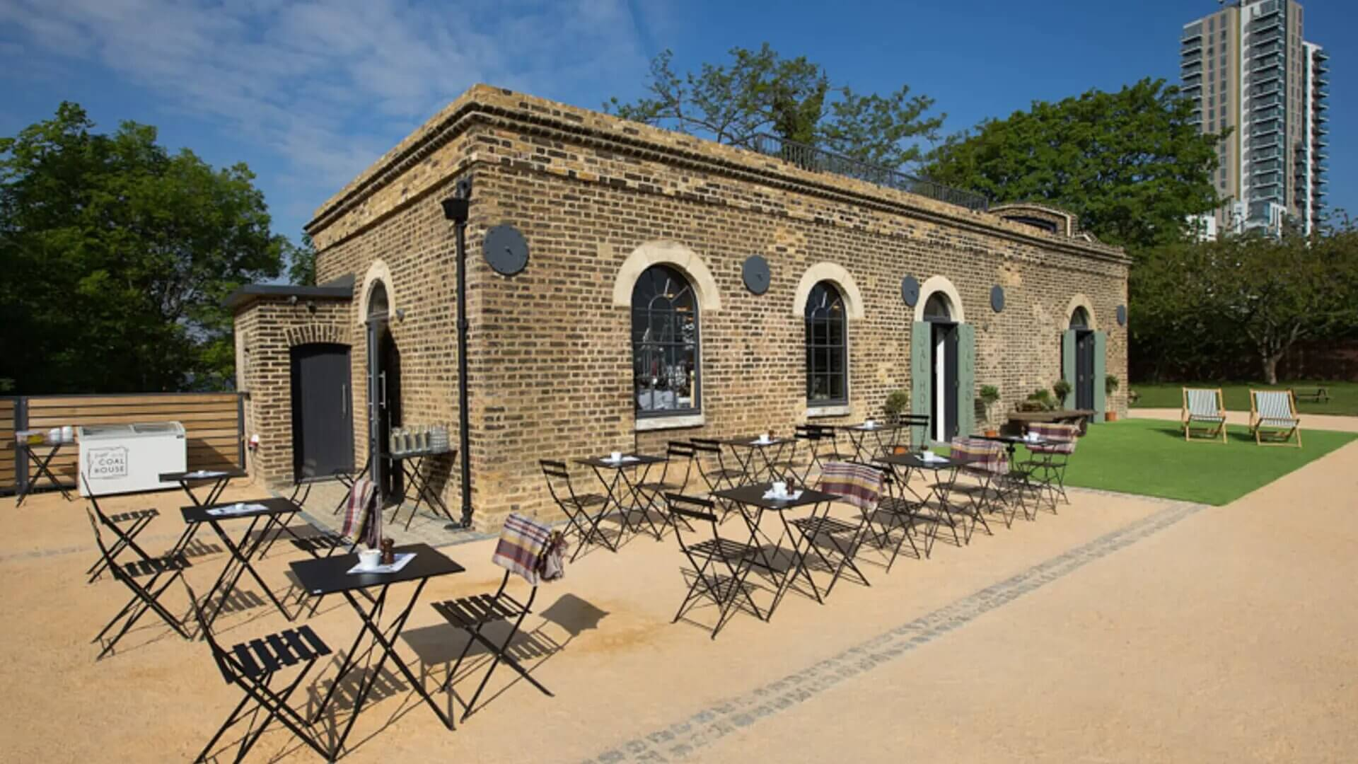 The outside view of The Coal House Cafe with tables outside it at Woodberry Wetlands.