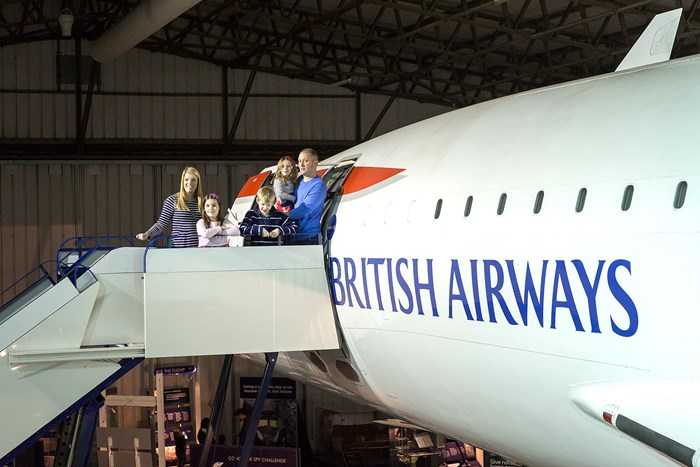 A family standing at the top of the steps of The Concorde at the National Museum of Flight.