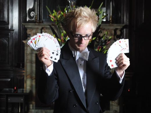 A magician fanning a deck of cards in each hand.