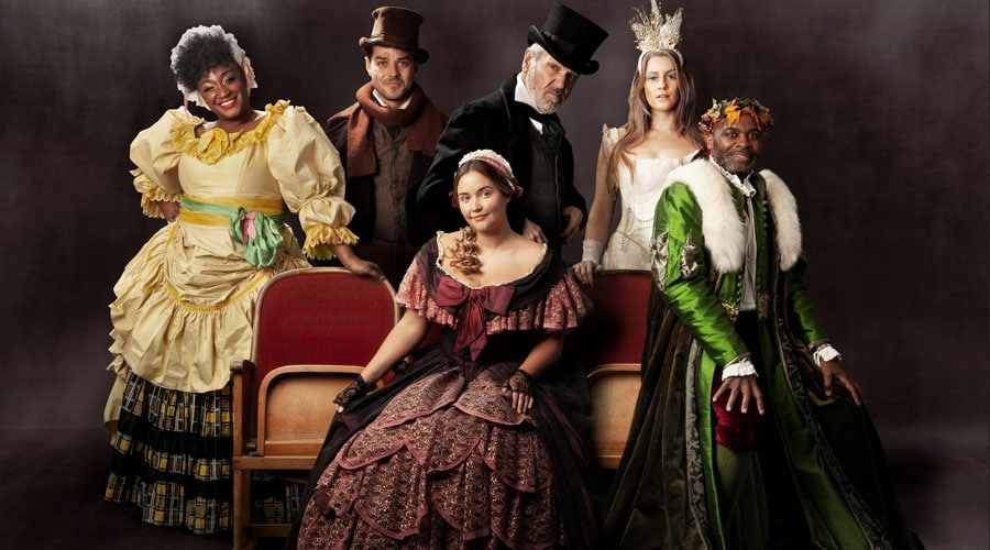The cast of the show A Christmas Carol standing up and seated in a promotional poster.