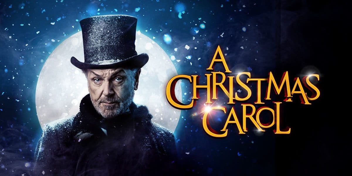 Brian Conley standing in front of a full moon wearing a top hat in the promo poster of A Christmas Carol.