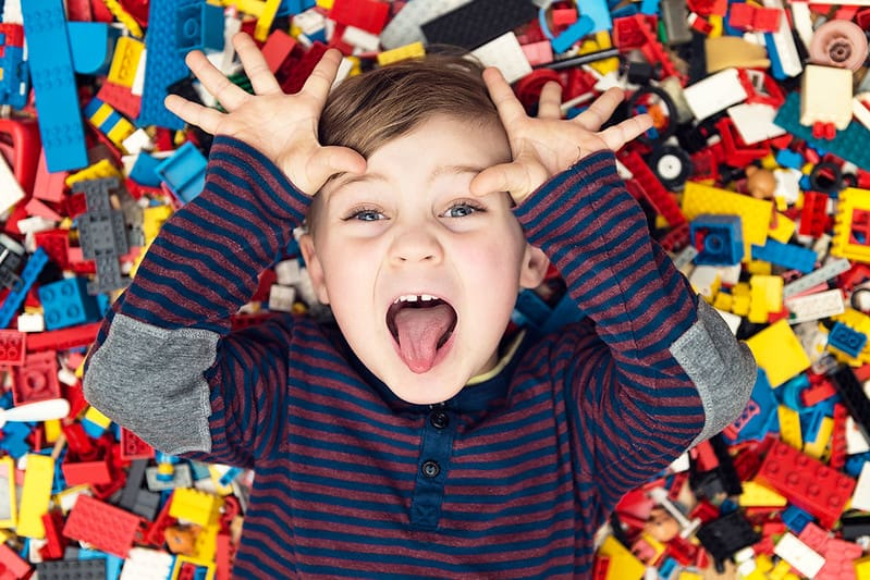 Boy in stripe long sleeve is lying down in the set of lego blocks.