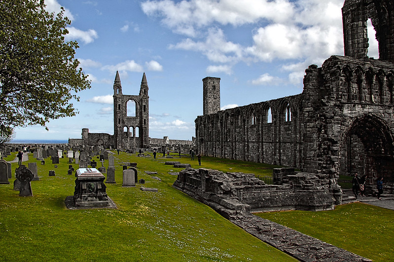 Ruins of the St Andrews Cathedral with green grass against a blue sky.