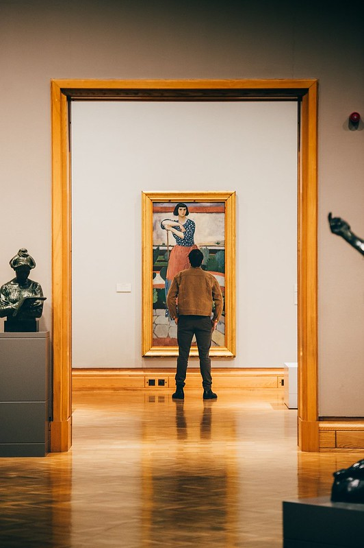 View through a series of doorways of a person looking at one of the paintings at National Museum Cardiff.