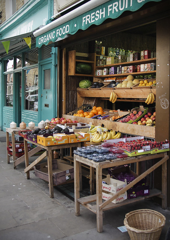 A fruit stand at Broadway Market with oranges on it.