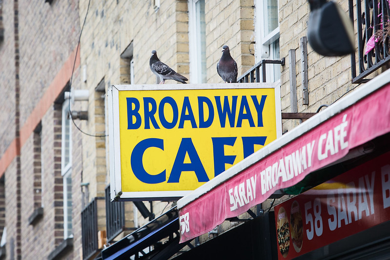 A yellow sign at Broadway Market reading 'Broadway Cafe' with pigeons sitting on it.