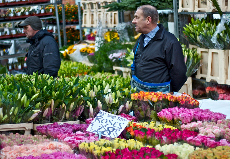 A man standing at his stall at Columbia Road Flower Market.