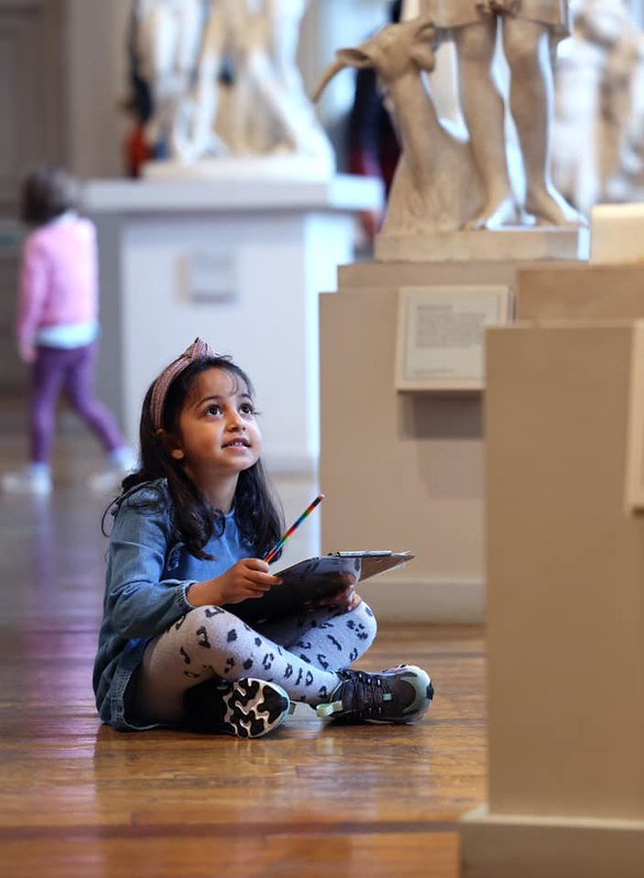 A young child drawing one of the statues at the Walker Art Gallery.