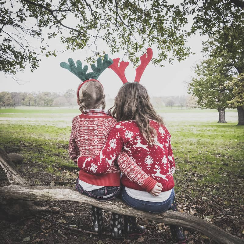 Sister's wearing Christmas jumpers sitting on a bench.