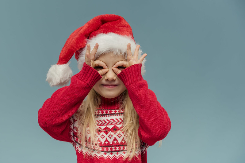 Little girl wearing Christmas Santa hat.
