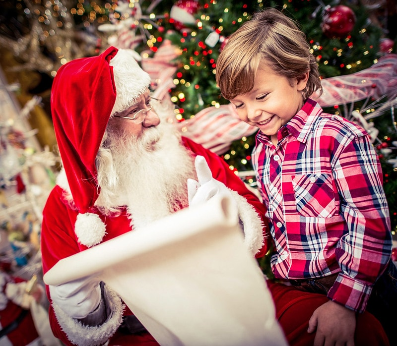 Child telling Santa what toys are at the top of their list.